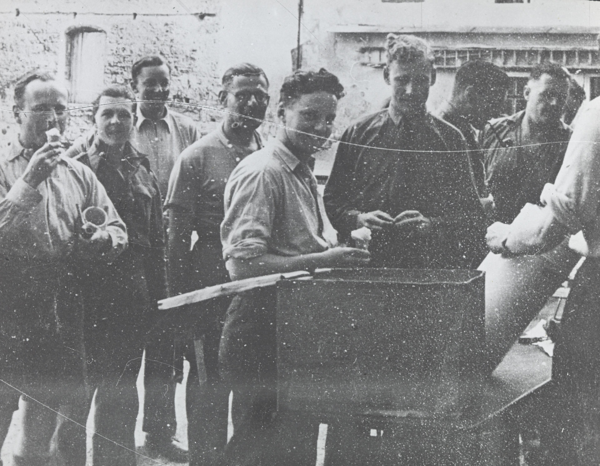 Unidentified prisoners of war camp: Group of men eating ice-cream