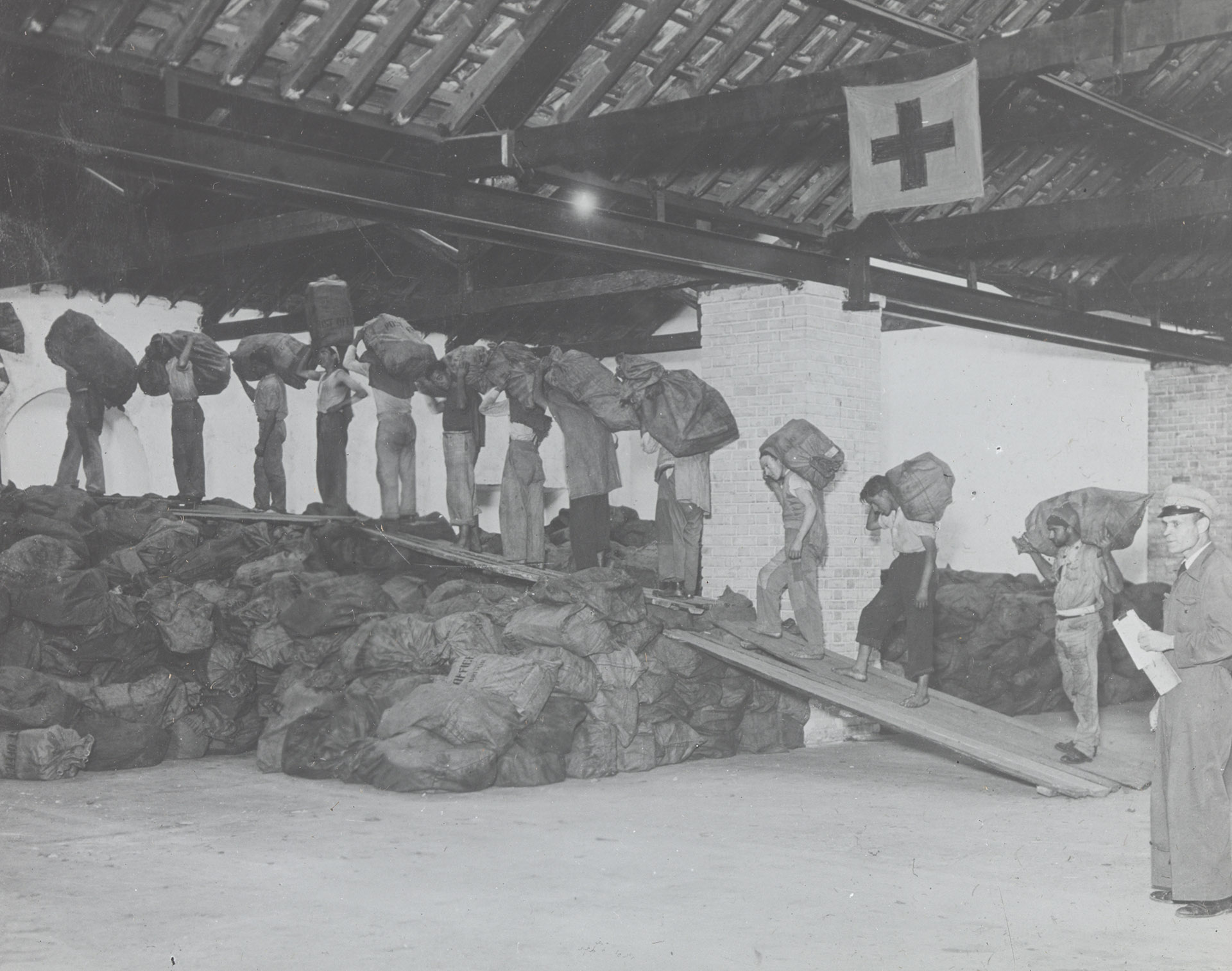 Men carrying Red Cross parcels in single file